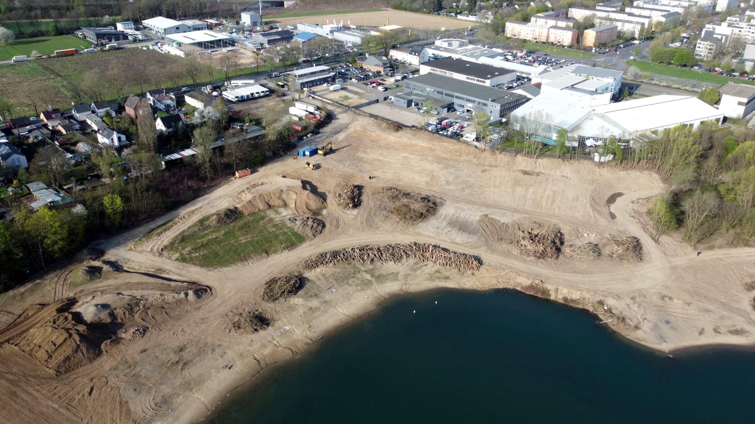 Ein Luftbild des südwestlichen Ufers des Rather Sees. Darauf sind gefällte Bäume auf Stapeln zu sehen und eine große, planierte Fläche, auf der einmal der Parkplatz entstehen soll.