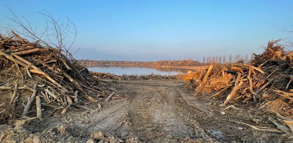 Im Vordergrund sind mehreren Reihen mit hohen Wällen aus Erdreich und gefällten Bäumen zu sehen. Dazwischen verlaufen Reifenspuren schwerer Baufahrzeuge. Im Hintergrund sieh man den Rather See.